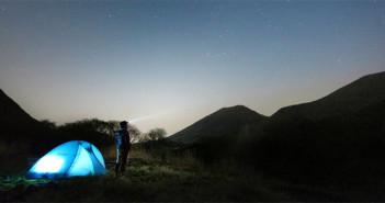 Ein Mann steht vor einem Zelt und schaut in den sternenklaren Nachthimmel.