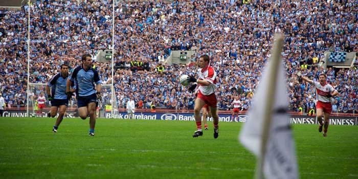 Ein Gaelic Football Spiel: Ein Angreifer läuft mit dem Ball auf das gegenerische Tor zu. Ein Verteidiger versucht ihn daran zu hindern.