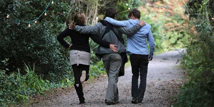 Drei Freunde schlendern Arm in Arm durch den Wald