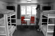 Eine Frau in einem Mehrbettzimmer in einem Hostel, die gerade ihr Bett macht. Das Bild ist schwarz weiß, nur zwei Stühle sind rot.
