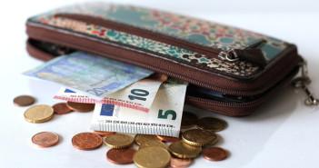 Ein Geldbeutel, vor dem Euro in Scheinen und Münzen ausgebreitet liegen