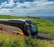 Ein Bus auf einer Küstenstraße. Im Hintergrund ein herrliches Panorama auf Irlands See.