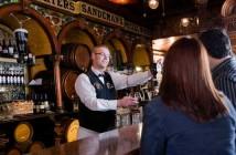 Ein Pub in Irland. Der Wirt steht hinter dem rustikalen Dresen und unterhält sich mit einer Frau und einem Mann.
